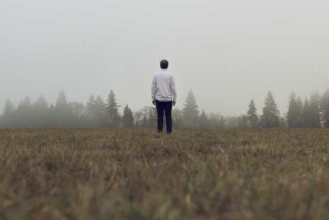 Foto met persoon op de rug ggezien in leeg landschap