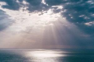 "Foto wolkenlucht boven zee met ""hemels"" zonlicht"